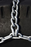 Chains on a Tire. Snow chains on heavy equipment tires stock photo