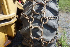 Chains on the tire of a snowplow in alaska. Stock Photo