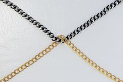 Chains on white leather background royalty free stock photo