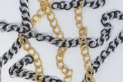 Chains on white leather background. Silver and gold color chains royalty free stock photography
