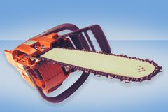 Chainsaw. Isolated chainsaw on a blue background Royalty Free Stock Image