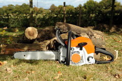 Chainsaw. Photograph of a chainsaw and logs stock photos