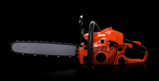Chainsaw. New red chainsaw isolated on black royalty free stock image