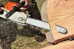 Chainsaw blade cutting log of wood stock photos
