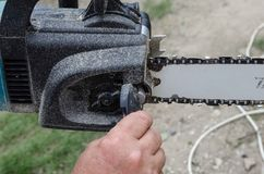 A chainsaw chain adjustment. Adjust the chain of a chainsaw by worker Royalty Free Stock Image