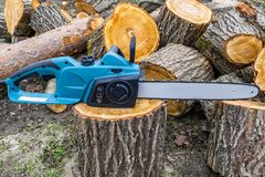 Chainsaw. Close-up of woodcutter sawing chain saw. Close up professional chainsaw blade cutting log of wood. Chainsaw bar Stock Image