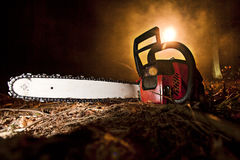 Chainsaw. And the dark woods Stock Photo