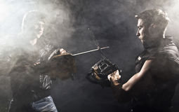 Chainsaw fight. Between two men and abstract smoke stock photos