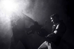 Chainsaw fight. Between two men and abstract smoke royalty free stock photo