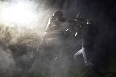 Chainsaw fight. Between two men and abstract smoke royalty free stock image