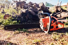 Chainsaw in front of a pile of wood logs. Orange chainsaw standing on the soil ground in front of a pile of wood logs stock photo