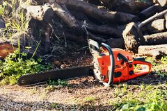 Chainsaw in front of a pile of wood logs. Gasoline powered professional chainsaw in front of a pile of wood logs stock photography