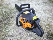 Chainsaw on frosty grass. A chainsaw sitting on frosty grass Stock Photos