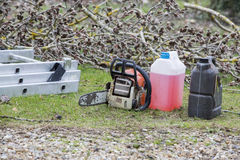 Chainsaw gasoline oil. Chainsaw and canister of gasoline and motor oil Royalty Free Stock Images