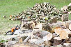 Chainsaw with cut firewood. Chainsaw on the ground beside piles of freshly cut firewood stock photos