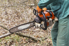 Chainsaw in a hands. Chainsaw in a hand of the lumberjack stock image