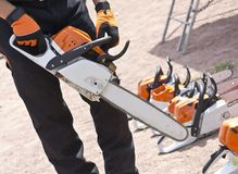Chainsaw  hands of men. Chainsaw in the hands of men Royalty Free Stock Photo