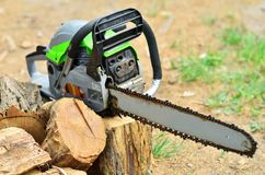 The working chainsaw lies on the stump. Chainsaw is lying on the stump next to the firewood royalty free stock image