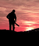 Chainsaw massacre. Man silhouette holding chainsaw at bloody sunset stock photos