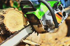 The chainsaw reaches the end of the wood. The photos are in the process stock photos