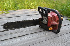 Chainsaw. Chainsaw with a red body. It should be on the floor of wooden planks. In the background is green. / Chainsaw / Feodor Eremin stock photos