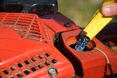 Chainsaw Refueling. A close up image of a old red chainsaw being refueled stock image