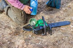 Chainsaw refueling with gasoline and oil. For further work royalty free stock photography