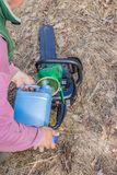 Chainsaw refueling with gasoline and oil. For further work stock photography