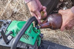 Chainsaw refueling with gasoline and oil. For further work royalty free stock photos