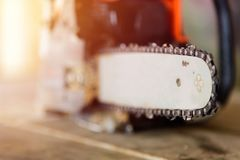 Focus to chainsaw with sunlight. Chainsaw with sunlight on wood plate stock image