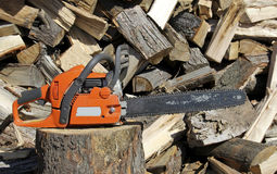 Chainsaw on a Woodpile Royalty Free Stock Photos