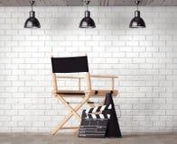 Chair主任,电影拍板和扩音机在砖Wa前面 免版税库存照片