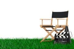 Chair主任,电影拍板和扩音机在草 3D rende 免版税图库摄影
