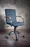 Chair. Office chair with armrests on a stone background Royalty Free Stock Images
