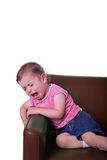 Chair. A little girl crying on a brown leather chair with a white background Royalty Free Stock Photography