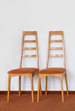 Chair. Two modern wooden chair. White wall and brown floor Stock Photos