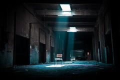 Chair on Abandoned Place With a Spotlight Coming from Outside Royalty Free Stock Images