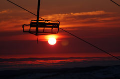 Chair Against a Blood Sunrise. Early morning tropical sunrise view through a chair lift on Mt Perisher, New South Wales, Australia Royalty Free Stock Images