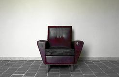 Chair against wall. Leather chair against white wall on gray tile floor Royalty Free Stock Image