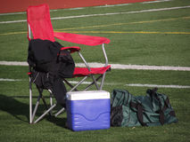 Chair and athletic gear on football field Royalty Free Stock Photos