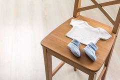 Chair with baby clothes stock photography