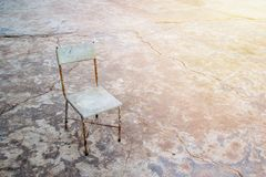 Chair on the background of an old concrete wall. With cracks stands on a cement floor background, space for text and design. tone with sunlight Stock Photos