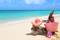 Chair with bag, hat, flip-flops and sunglasses on sunny beach, t Royalty Free Stock Image