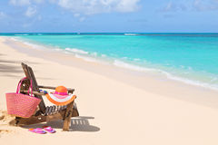 Chair with bag, hat, flip-flops and sunglasses on sunny beach, t Stock Photography