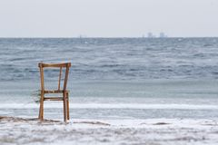 Chair and Barsebäck in the horizon. Chair washed ashore from the sea onto Amager Strand. Barseba?ck nuclear power plant in Sweden is seen in the background Royalty Free Stock Images