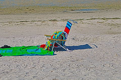 Chair on the Beach. Brightly colored towels are scattered as the occupants went to the water.  The shadow of the multi-colored chair is in the sand. This is at Royalty Free Stock Images