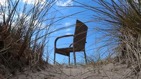 Chair on the beach. Chair on a sand dune stock footage