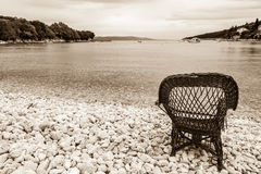 Chair on a beach covered with pebbles Royalty Free Stock Photos