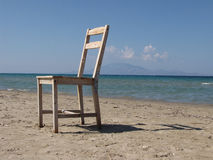 Chair on the beach. Old wooden chair on the beach and sea in background Stock Photography