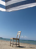 Chair on the beach. Old wooden chair on the beach and sea in background Stock Photos